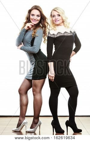 Generation fashion elegant outfit concept. Adult daughter with mother in full lenght. Two slim women wearing dresses high heels shoes long hair blonde mom and brown haired girl