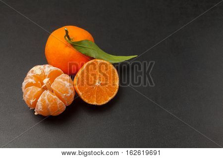 Tangerines on black background in studio up view