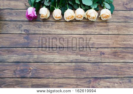 series of seven roses six white roses and a one pink rose on top of a wooden background