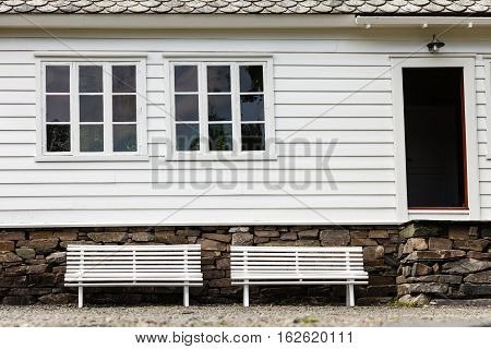 Place to relax concept. Symmetrical two white bench in front of traditional scandinavian light wooden house with windows.