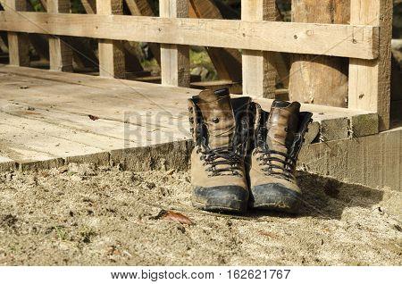 Old tourist hiking shoes on a bridge. Selective focus