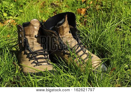 Old tourist hiking shoes in the grass.