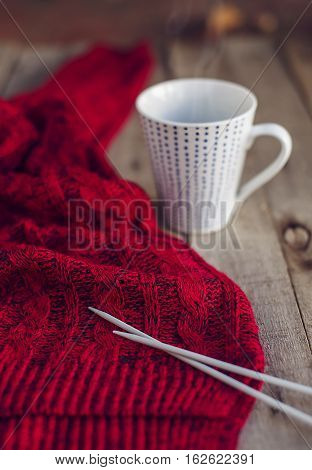Beautiful red knitted sweater needles and cup of hot tea on wooden table. Cozy winter. Hobbies. Selective focus.