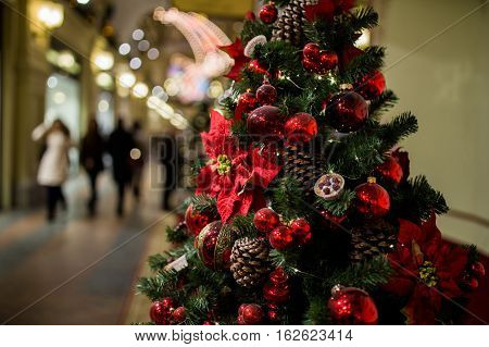 Shopping center with Christmas tree decorated with cones, flowers and red balls