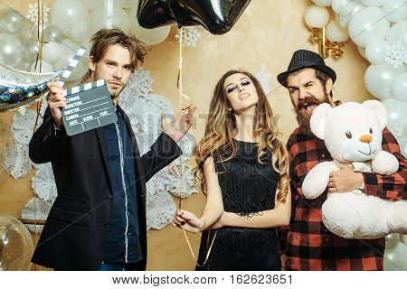 happy christmas people of pretty sexy woman or cute girl in glamour dress bearded man in hat and handsome guy holds plush bear toy and clapperboard near balloons and decorative new year snowflakes