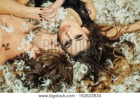 sexy christmas couple of pretty sexy woman or cute girl with long hair and fashionable makeup handsome man with bare chest hold hands lying on white feathers as decorative new year snowflakes