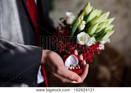 wedding bands wedding rings in the red box wedding jewelry wedding preparation groom holding a red box with wedding rings flowers