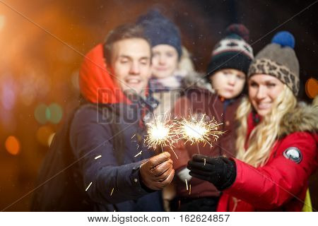 Family with children with sparklers in park at night in Christmas