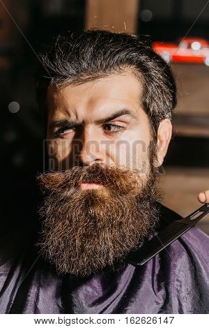 Handsome bearded man hipster brunette with beard and moustache has haircut or clippering in hairdressing saloon or barbershop. Barber works with comb