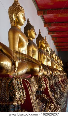 A row of seated meditating golden Buddhas in a Thai temple.
