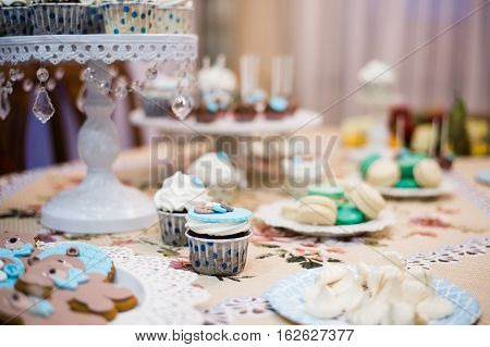 Dessert table for a party. Ombre cake, cupcakes, sweetness and flowers.