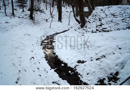 Mountain river flowing among the slopes and trees covered with white snow