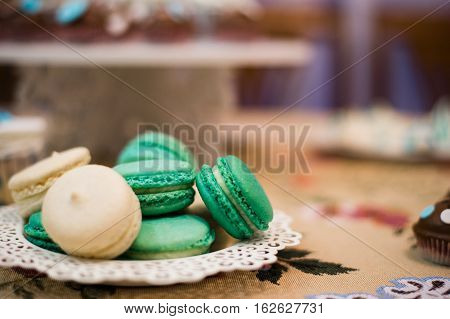 White cupcakes and green macaroons on the white dish.