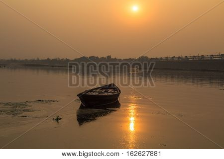 Solitary wooden boat at sunset in the water of river Damodar, Durgapur Barrage, West Bengal, India.