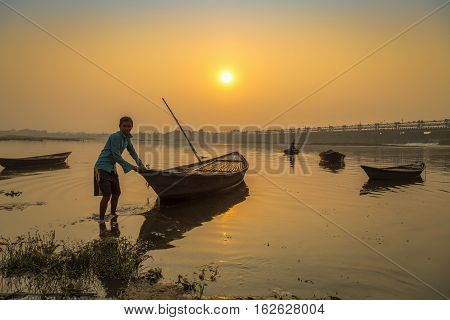 DURGAPUR, INDIA - DECEMBER 20, 2016: An oarsman tries to tow his boat to shore at sunset on river Damodar near the Durgapur Barrage, West Bengal, India.