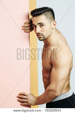 Handsome man or muscular macho bodybuilder with bristle hairstyle sexy muscle torso body with triceps biceps poses on pink door
