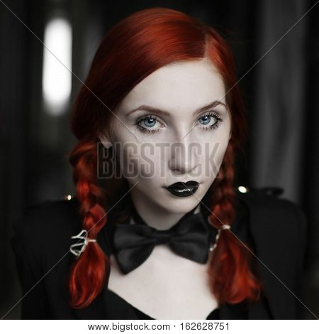Portrait of red-haired girl in bow tie on a dark background gothic style girl with pigtails a girl in a black dress fashion style sense of style girl in dress and in a black cloak black coat black lips sitting