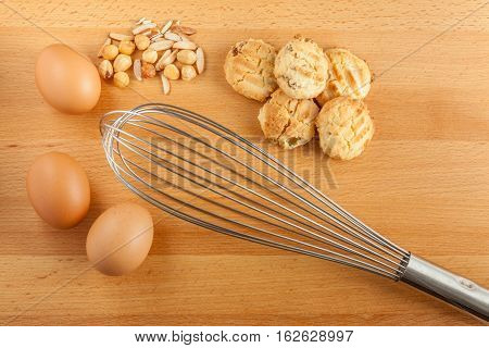 Baking cookies ingredients fresh eggs mixed nuts and manual hand eggs beater.