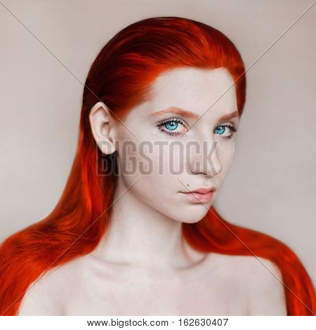 portrait of long-haired naked red-haired girl on white
