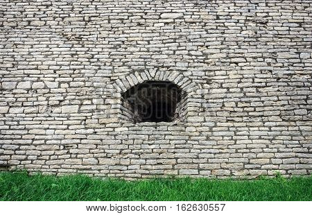 Background of old gray stone wall in Krom (Kremlin) of Pskov with embrasure