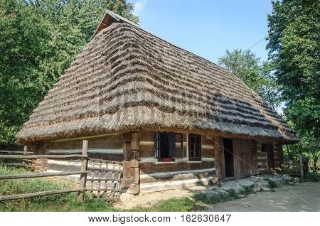 Lviv Ukraine - September 09 2016: Old Ukrainian authentic wooden house with thatched roof from Mshanets village Lviv region Ukraine. Now in Museum of Folk Architecture in Lviv