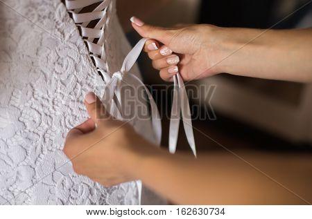 tighten wedding dress on bride, white gown