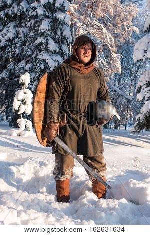 Swordsman in the winter forest in historical