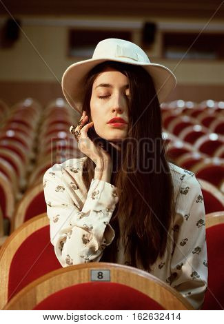 portrait of a pretty girl hipster in a movie theater wearing hat, dreaming alone close up