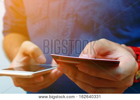 Close Up Of Young Man Use Smart Phone And Holding Credit Card, Shopping Online Concept.