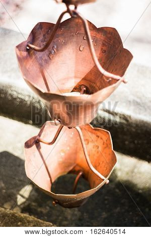 Vintage metallic bells used for rain waters way-out in zen garden stock photo