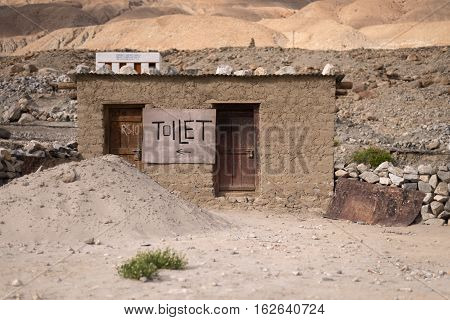 Old house in desert with Toilet sigh board in Ladakh