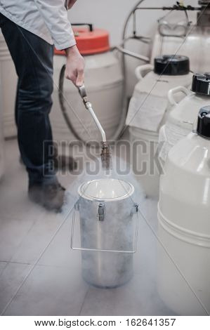 Liquid Nitrogen Technician Fills Cryogenic Container