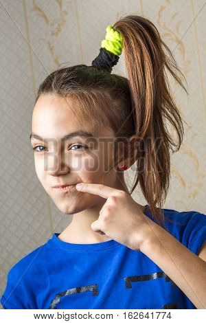 11 Year Old Girl Looks Slyly Squinting Sideways, Leaning A Finger To Her Cheek.
