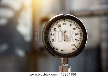 Closeup of industrianl manometer measuring gas pressure on the plant. Power generation pipes and valves on the blurred background.