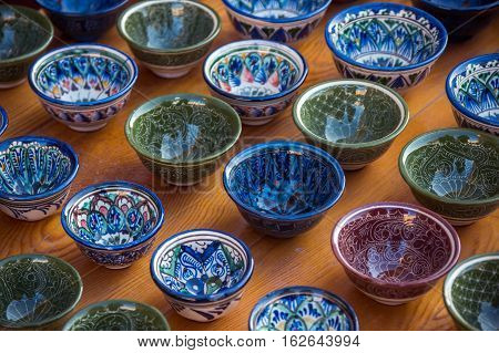 Rows of cups with traditional uzbekistan ornament on a street market of Bukhara Uzbekistan Central Asia. Silk Road
