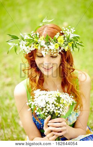 Attractive girl in flower crown looking at wildflowers bouquet