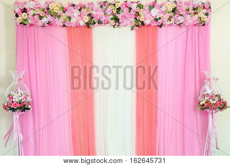 Colorful backdrop of fake flowers with pink and white fabric arrangement by handmade ready for wedding ceremony.