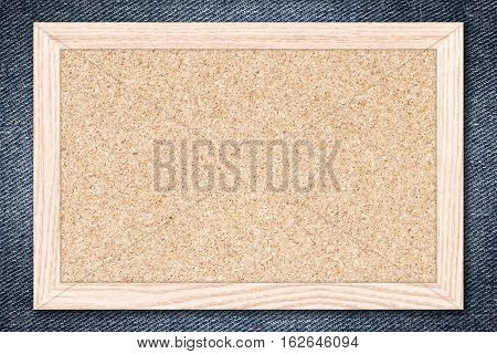 Cork board or Empty bulletin board with a wooden frame on denim jeans background for design with copy space for text or image.