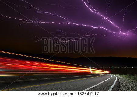 Lighting Strike With Long Exposure Traffic Trails Under Stormy Sky.