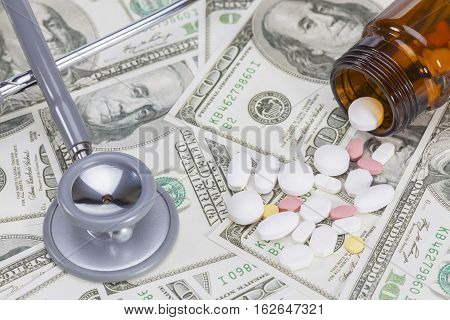 Stethoscope and Medicine tablets on money, business concept