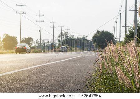 Car on an asphalt road between field in the rural landscape.