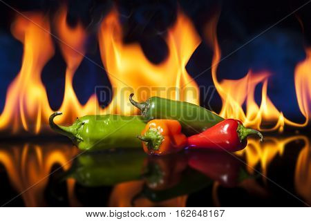 Chili Peppers with fire in the background. Shallow depth of field with focus on the jalapeno. Peppers are on reflective surface.