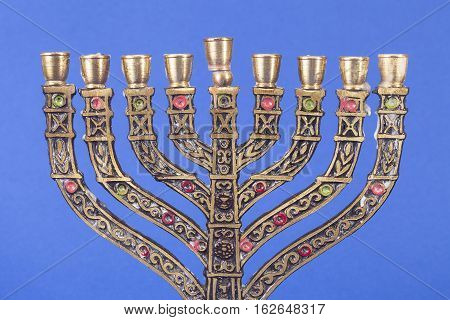Nine branched menorah isolated on blue background.