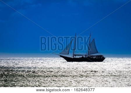Sailboat On Sea Navigating Towards The Sunset