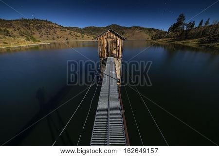 Heenan Reservoir With Damn Gate Building At Night With Stars. Lit By Moonlight.