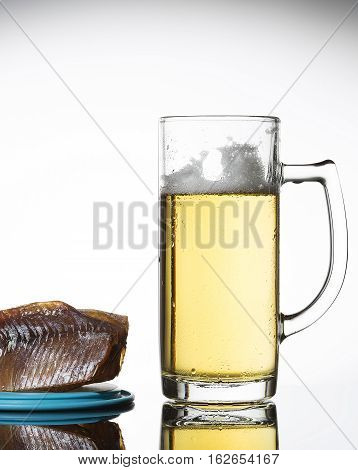 Glass of beer and salty fish on a white background