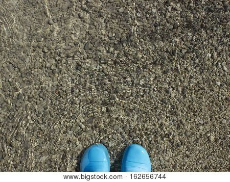 blue galoshes standing in the cold clear water on the pebbly bottom
