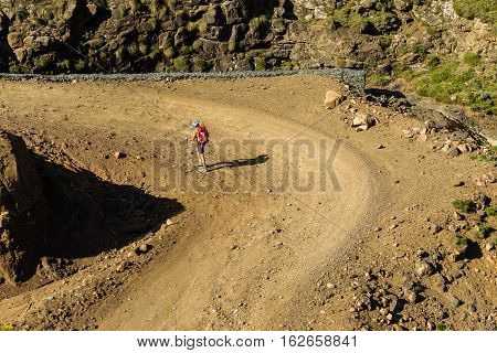 Hiker hiking walking up steep mountain dirt road pass landscape
