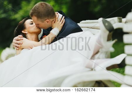 Bride Lies On The Knees Of Fiance On The Bench Somewhere In The Park