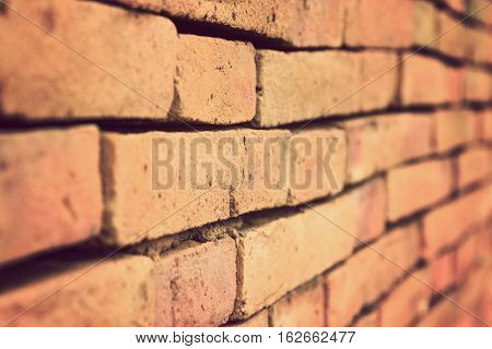 Terracotta brick wall shown in one point perspective with selective focus and shallow depth of field in vintage retro color style